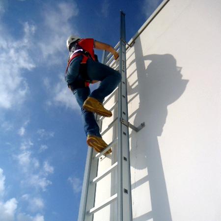 Operatore che sale una scala poggiata su una parete