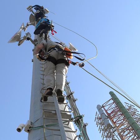 Operatori intenti al lavoro su torre per ponti radio